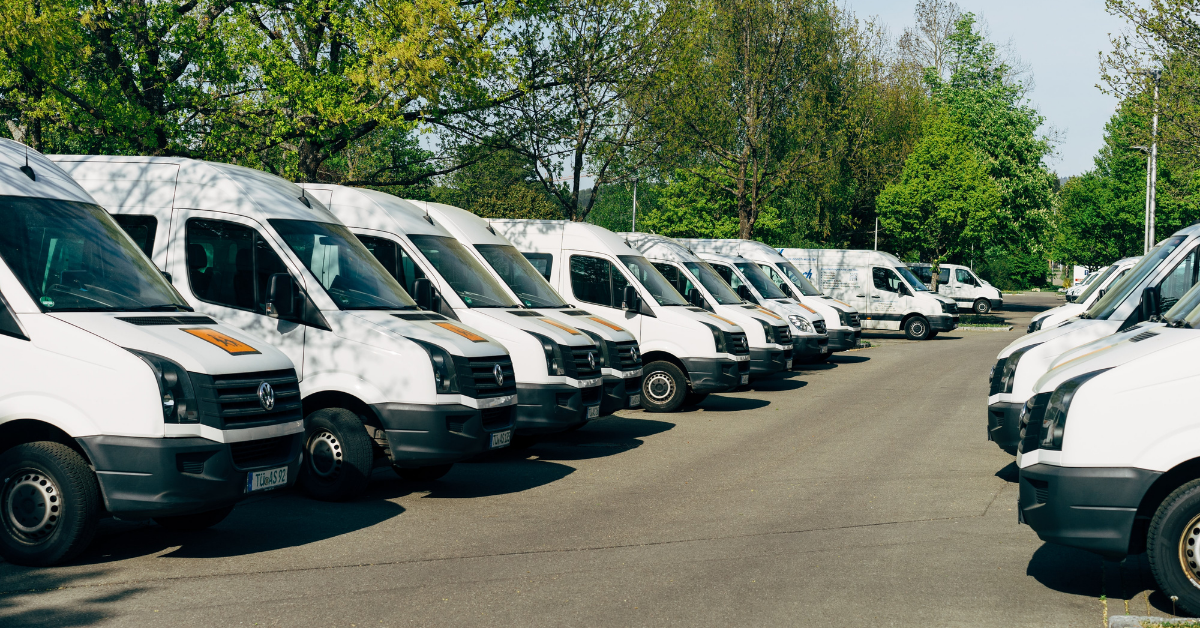 a parking lot of a lot of white vans